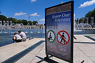 WASHINGTON - JUNE 30, 2019: A sign tells visitors to not walk in the fountain as visitors cool off at the World War II Memorial fountain June 30, 2019, in Washington, D.C.