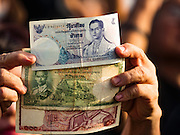 22 NOVEMBER 2016 - BANGKOK, THAILAND: People hold up Thai currency, which bears a likeness of the late King of Thailand during a ceremony to honor His Majesty at Sanam Luang Tuesday. Hundreds of thousands of Thais gathered across Thailand Tuesday to swear allegiance to the Chakri Dynasty, in a ceremony called Ruam Phalang Haeng Kwam Phakdi (the United Force of Allegiance). At Sanam Luang, the Royal Parade Ground, and location of most of the mourning ceremonies for the late King, people paused to honor His Majesty by singing the Thai national anthem and the royal anthem.       PHOTO BY JACK KURTZ