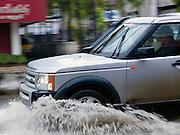 A 4x4 vehicle drives through flooded streets during the monsoon season, Cochin, Kerala, India