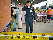 26 JUNE 2011 - CHIANG MAI, THAILAND:   A Royal Thai Police officer stands guard at the Chiang Mai voting center during absentee voting Sunday. More than 30,000 police officers have been mobilized to provide election security. Absentee voting was Sunday, July 26 in Thailand's national election. The regular voting is Sunday July 3. In Chiang Mai, center of the powerful Red Shirt opposition movement and their legal party Pheua Thai, turnout was heavy despite a steady rain. Thailand's democracy will be tested in the election, which is the most bitterly fought contest in Thai political history. The Pheua Thai represents people loyal to fugitive former Prime Minister Thaksin Shinawatra, ousted by a military coup in 2006. The ruling Democrats have governed Thailand in one form or another nearly continuously since 1932. Pre-election polls show Pheua Thai leading but not by enough to rule without forming a coalition with smaller parties.  PHOTO BY JACK KURTZ