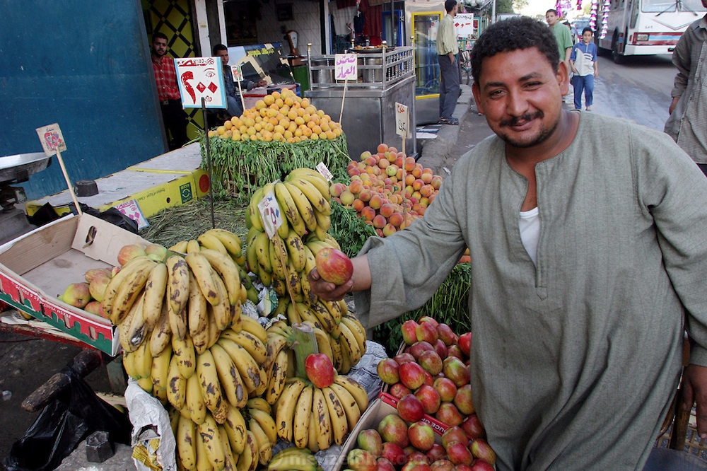 A proud Cairo fruit-stand owner shows off his produce. Cairo, Egypt.