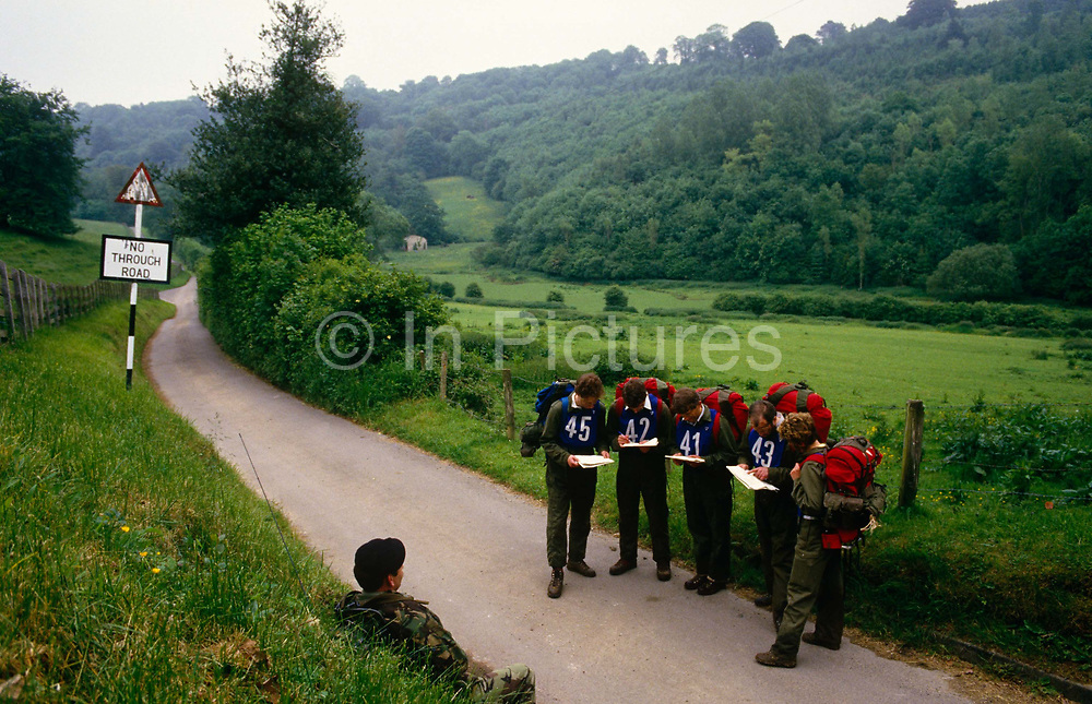 Deep in the West Sussex countryside are a group of Territorial Army soldiers. They have stopped in a remote lane to consult their Ordnance Survey maps during a day of learning to navigate with maps and compasses. Over a weekend learn the skills needed to be part-time army volunteers known as the TA and have far to go. Together they look at maps and argue where they should go next. Looking on with mild amusement is their senior officer who accompanies them to assess their leadership skills and initiative. Behind them a road sign tells them the road ahead is a dead end to traffic. It is a very English summer landscape of lush green vegetation and grasses. The TA work as part of Britain's reserve land forces. Together with the Regular Army they provide support at home and overseas including Iraq and Afghanistan. .