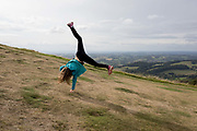 A young girl cartwheels near the summit of The Beacon, on 15th September 2018, in Malvern, Worcestershire, England UK. Worcestershire Beacon, also popularly known as Worcester Beacon, or locally simply as The Beacon, is a hill whose summit at 425 metres 1,394 ft[1] is the highest point of the range of Malvern Hills that runs about 13 kilometres 8.1 mi north-south along the Herefordshire-Worcestershire border, although Worcestershire Beacon itself lies entirely within Worcestershire.