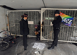 © Licensed to London News Pictures. 21/01/2012, London, UK. A woman leaves the building via a side entrance watched by police. Occupy London protesters this morning publicly repossessed Roman House, an abandoned nine-storey office building in the Barbican. The Occupy London campaigners - part of the global movement for social and economic justice and real democracy - stated that they intend to occupy the building - their fifth occupation - until such time as the City of London Corporation publishes full details of its City Cash Accounts.  Photo credit : Stephen Simpson/LNP
