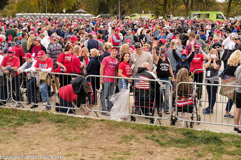 14 OCTOBER 2020 - DES MOINES, IOWA: People wait to get into a campaign rally for President Donald Trump. About10,000 people were expected at the Des Moines International Airport for a campaign rally supporting the reelection of President Trump. Trump spoke at the rally, despite testing positive for COVID-19 less than three weeks ago. The rally did not meet the CDC guidelines for a safe gathering in the time of Coronavirus and violated Iowa's health emergency declarations barring gatherings of more than 25 people. This week Iowa exceeded 101,000 cases of COVID-19 and a surge in hospitalizations for COVID-19.       PHOTO BY JACK KURTZ