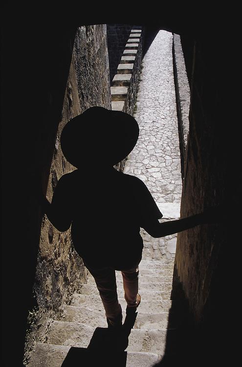 Europe, Portugal, Lisbon, woman descending stairs in historic Castelo de Sao Jorge.  MR