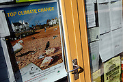 Information about Climate Change and the community are affixed on one of the doors in BedZED, on Thursday, Sep. 6, 2007. BedZED or the Beddington Zero Energy Development, is an environmentally-friendly housing development near Wallington, England in the London Borough of Sutton. It was designed by the architect Bill Dunster who was looking for a more sustainable way of building housing in urban areas in partnership between the BioRegional Development Group and the Peabody Trust. There are 82 houses, 17 apartments and 1,405 square meters of work space were built between 2000. The project was shortlisted for the Stirling Prize in 2003. The project is designed to use only energy from renewable source generated on site. In addition to 777 square meters of solar panels, tree waste is used for heating and electricity. The houses face south to take advantage of solar gain, are triple glazed and have high thermal insulation while most rain water is collected and reused. Appliances are chosen to be water efficient and use recycled water wherever possible. Low impact building materials were selected from renewable or recycled sources and were all originating within a 35 mile radius of the site to minimize the energy required for transportation. Also, refuse collection facilities are designed to support recycling and the site encourage eco-friendly transport: electric and LPG cars have priority over petrol/diesel cars, and electricity is provided by parking spaces appositely built for charging electric cars.