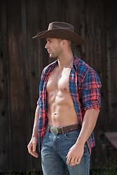 hot rugged muscular cowboy with an open shirt by a barn