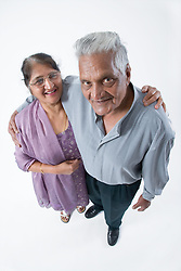 Portrait of an older man with his arms around his wife's shoulders,
