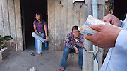 SEX INDUSTRY TOURISM. South East Asia, Cambodia, Phnom Penh. Taxi girls, prostitutes, serve foriegn tourists & Khmer, Cambodians. The sex industry is part of the fabric, servicing all classes of Cambodian society. Girls are forced into prostitution because of poverty and corruption that exists across the country. People might earn 1 to 2 $ per day, even less in rural areas, so the lure of prostitution is high. Families can sell young girls, virgins, for several hundred dollars. Cheap brothels line the streets in parts of the city centre, near railway tracks, and on the periphery. Sex for Cambodians at cheap prices in the street brothels, as low as 1 $ US, to exorbitant fees in penthouse hotel suites for the rich. Sex tourism industry attracts Western and Asian tourists typically paying 10 - 30 $ US. Expressions such as 'yam yam', eating, for a blowjob 'bam bam' for intercourse. There are 'lady-boys', youths, who use the money to pay for  sex change operations. Prostitutes spend lots of money on make-up, clothes, and mobile telephones. They live in squalor. Due to public advertising campaigns and outreach work, Aids and HIV cases have dramatically decreased, in Cambodia, since the late '90s. Condoms are encouraged, are cheap and widely available. This is seen as  a success story by medical and health authorities. There are risks as ex-prostitutes known as 'sweethearts' don't use condoms with their partners. Brothels, v & madams take their cut, but many taxi-girls work as free agents. Bars, pool halls or beer gardens have staff and taxi-girls available to service male clients, some work as barmaids or escorts. There is violence against prostitutes; gang-rape and murder by Khmer gangs. Once a girl has worked as a prostitute it is unlikely she can ever marry.///Policeman counting out his share of the brothel's earnings
