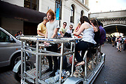 Friends out on a Pedi Bus in London UK. This is an eight seater bicycle which doubles up as a bar, so friends can sit cycling and laughing as they cycle and drink their way around the city.