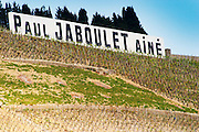 Sign saying Paul Jaboulet Aine.   The Hermitage vineyards on the hill behind the city Tain-l'Hermitage, on the steep sloping hill, stone terraced. Sometimes spelled Ermitage.  Tain l'Hermitage, Drome, Drôme, France, Europe