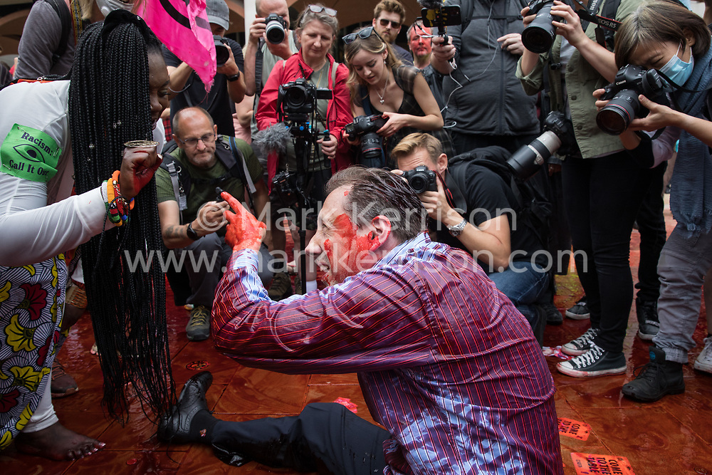 London, UK. 27th August, 2021. An Extinction Rebellion activist dressed as a financier covered in fake blood acts out a racist quarrel with United for Black Lives founder Marvina Newton in Paternoster Square following a Blood Money March through the City of London. Extinction Rebellion were intending to highlight financial institutions funding fossil fuel projects, especially in the Global South, as well as law firms and institutions which facilitate them, whilst calling on the UK government to cease all new fossil fuel investment with immediate effect.