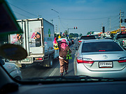 09 JANUARY 2019 - KANCHANABURI, THAILAND: A woman sells flower garlands to motorists in Kanchanaburi.       PHOTO BY JACK KURTZ