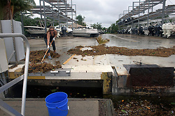 October 7, 2016 - Florida, U.S. - A worker with U-Tiki Beach restaurant cleans up the dock area Friday morning. The high tide left seaweed and assorted vegetation. (Credit Image: © Melanie Bell/The Palm Beach Post via ZUMA Wire)