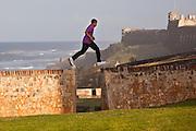 A young boy run along the old fortress wall of San Juan, Puerto Rico.