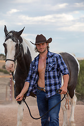 good looking cowboy outdoors on a ranch with his horse