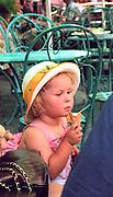 Girl age 4 eating ice cream cone in sidewalk cafe.  Warsaw Poland