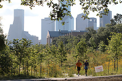 Couple enjoying a walk in Buffalo Bayou Park with the Houston skyline in the background.
