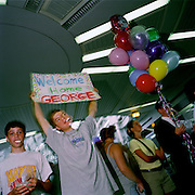 With others, a young man with a Welcome Home balloon meets a friend called George after a long absence, in the airport terminal at Chicago-O'Hare airport, Illinois, USA. The crowd of friends await the arrival of George in the public domain area of the airport hub, one of the largest airport in the United States - 12 months before the terrorist attacks on America that changed the public's attitude to flying on commercial airliners.