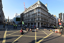"""© Licensed to London News Pictures. 19/04/2019. LONDON, UK.  Activists lie in the road in Regent Street to block the path of the pink boat being towed away from Oxford Circus during """"London: International Rebellion"""", on day five of a protest organised by Extinction Rebellion.  Protesters are demanding that governments take action against climate change.  Police have issued a section 14 order requiring protesters to convene at Marble Arch only so that the protest can continue.  Photo credit: Stephen Chung/LNP"""