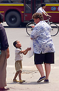 A poor child begs a foreigner for money near a popular tourist trap in Beijing.