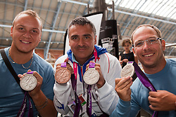 © under license to London News Pictures. 25/06/12..Nicolas Peifer, silver medalist in the men's tennis, Stephane Houdet, silver and bronze medalist in the men's tennis and Frederic Cattaneo, silver medalist in the men's tennis(left-right/) at the Eurostar as the French Paralympic team depart London on a specially charted Eurostar train...ALEX CHRISTOFIDES/LNP