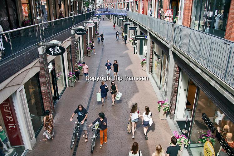Nederland, Nijmegen, 30-5-2020 Per 1 juni gaan nieuwe en versoepelde maatregelen in . Stadsbeeld van een winkelstraat in het centrum van de stad . Nu de drukte toeneemt vanwege het mooie weer en het langdurige thuisblijven, binnenzitten, is het straatbeeld drukker . Mensen zijn aan het winkelen en staan in de rij bij de winkel in de openlucht om hun beurt af te wachten . Winkels hebben desinfectiegel ter desinfectie van de handen bij de ingang staan . Foto: Flip Franssen