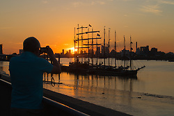 Woolwich, London, September 14th 2016. The sun sets behind the skyscrapers of Docklands and the Tall ships gathered for the Sail Greenwich Festival 2016 on the River Thames at Woolwich.  ©Paul Davey<br /> FOR LICENCING CONTACT: Paul Davey +44 (0) 7966 016 296 paul@pauldaveycreative.co.uk