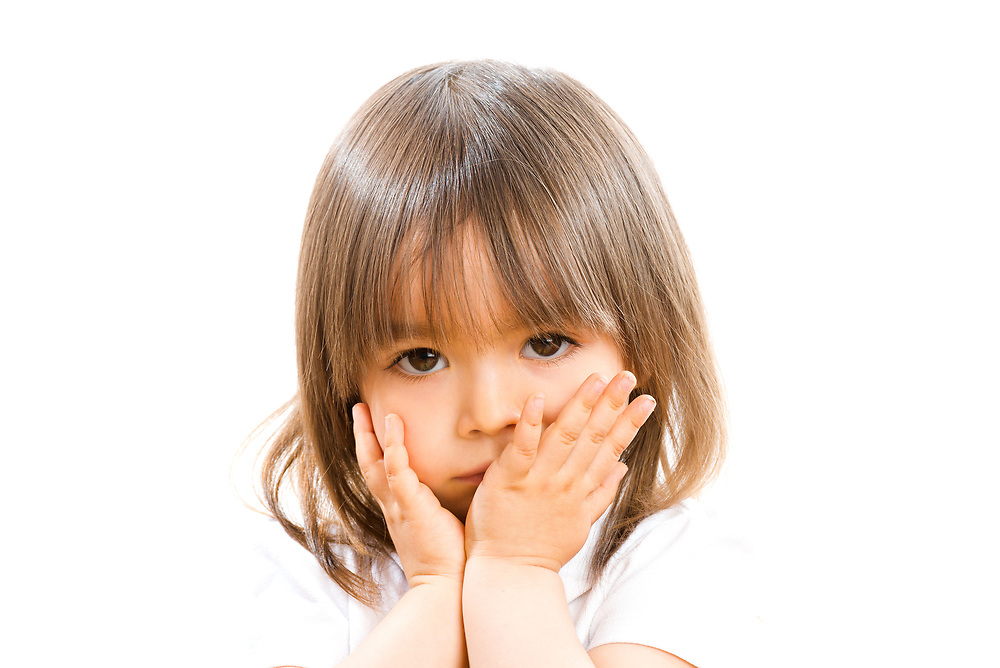 Two years old girl with hands in front the face on white background.