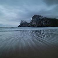 Incoming wave flows over Kvalvika beach on a rainy summer evening, Moskenesøy, Lofoten Islands, Norway