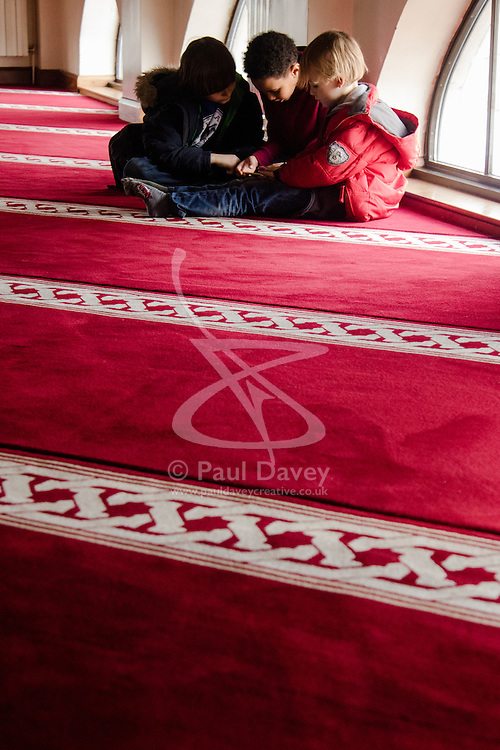 """Finsbury Park Mosque, London, February 7th 2016. Whilst their parents watch Muslims at prayer during a tour of Finsbury Park Mosque, three little boys are absorbed by a game on a smartphone during the Visit My Mosque initiative by the Muslim Council of Britain to show non-Muslims """"how Muslims connect to God, connect to communities and to neighbours around them"""".<br /> . ///FOR LICENCING CONTACT: paul@pauldaveycreative.co.uk TEL:+44 (0) 7966 016 296 or +44 (0) 20 8969 6875. ©2015 Paul R Davey. All rights reserved."""