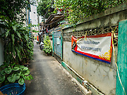 02 NOVEMBER 2016 - BANGKOK, THAILAND:  The front gate to the spirit house workshop on a narrow line in Ban Fuen. There used to be 10 families making traditional spirit houses out of teak wood in Ban Fuen, a community near Wat Suttharam in the Khlong San district of Bangkok. The area has been gentrified and many of the spirit house makers have moved out, their traditional wooden Thai houses replaced by modern apartments. Now there is just one family making the elaborate spirit houses. The spirit houses are made by hand. It takes three days to make a small one and up to three weeks to make a large one. Prices start at about $90 (US) for a small one. The largest, most elaborate ones can cost over $1,000 (US). Almost every home and most commercial buildings in Thailand have a spirit house, which is a shrine to the protective spirit of a the land. Spirit houses are also common in Burma, Cambodia, and Laos.       PHOTO BY JACK KURTZ