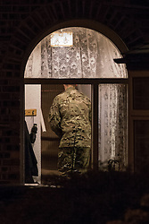 © Licensed to London News Pictures . 28/11/2013 . Manchester , UK . A man in army fatigues walks inside the house with bags and a torch . Scene at 17 Mellor Street in Eccles , Greater Manchester this evening (Thursday 28th November 2013) where police have cordoned off adjoining streets and evacuated houses following the discovery of a suspicious device .  Photo credit : Joel Goodman/LNP