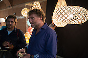 Joe Trubridge, center, with his pendant lamps made of bamboo, laminated wood, and aluminum. Many of the lamps can be assempbled by the buyer.