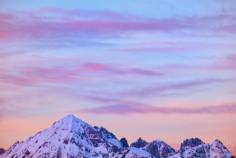 A band of cirrus clouds take on pastel colors at sunset in the sky over Mount Larrabee and the Boulder Peaks in the North Cascades of Washington state. Mount Larrabee, which stands 7,865 feet (2,397 meters) is part of the Skagit Range, which is a sub-range of the North Cascades. It is located less than a mile and a half south of the Canadian border and was originally known as Red Mountain. During the summer months, its red peak, caused by the oxidation of iron in its rock, is distinct.