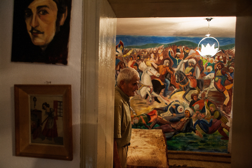 Slavko Spasic in his bedroom in the Serbian enclave of Velika Hoca, Kosovo with a painting of the 1389 Battle of Kosovo. August 2010.