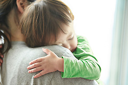 Lifestyle image of Asian baby girl sleeping on mother's shoulder