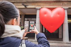 """© Licensed to London News Pictures. 14/02/2018. LONDON, UK. A tourist takes a photo of a giant chubby heart balloon at Covent Garden as part of """"Chubby Hearts Over London"""",  a design project conceived by Anya Hindmarch.  Supported by the Mayor of London, the British Fashion Council and the City of Westminster giant chubby heart balloons will be suspended over (and sometimes squashed within) London landmarks as a declaration of love to the city starting on Valentine's Day and continuing throughout London Fashion Week.   Photo credit: Stephen Chung/LNP"""