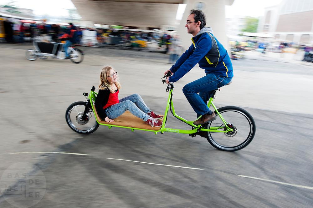 Een meisje wordt vervoerd met een transportfiets. In Nijmegen vindt voor de derde keer het International Cargo Bike Festival plaats. Het tweedaags evenement richt zich op het gebruik en de gebruikers van bakfietsen. Bakfietsen worden in heel Europa steeds vaker ingezet, zowel door particulieren als bedrijven. Het is een duurzame vorm van transport en biedt veel voordelen.<br /> <br /> In Nijmegen for the third time the International Cargo Bike Festival is hold. The two-day event focuses on the use and users of cargobikes. Cargo bikes are increasingly being deployed across Europe, both individuals and businesses. It is a sustainable form of transport and offers many advantages.Nederland, Nijmegen, 13-04-2014