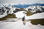 Jon Duke descends a snow field as snow-capped mountains extend beyond into Canada, Mount Baker Wilderness, Washington.