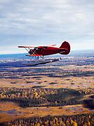 Jimmy Branham's 1934 Waco biplane on floats flying west of the Yentna River, Alaska.