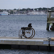 Wheelchairs left on the dock during the C. Thomas Clagett, Jr. Memorial Clinic & Regatta at Newport, Rhode Island hosted by Sail Newport at Fort Adams. <br /> The Clagett is North America's premier event for sailors with disabilities with sailors competing in the 3 Paralympic class boats and is an integral part of preparation for athletes preparing for  Paralympic and world championship racing. Newport, Rhode Island, USA. 26th June 2015. Photo Tim Clayton