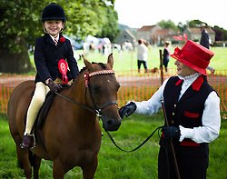© Licensed to London News Pictures. <br /> 29/07/2014. <br /> <br /> Kirkbymoorside, United Kingdom<br /> <br /> A young girl prepares for her round during the Ryedale agricultural show in North Yorkshire. The show was established in 1855 and is a traditional agricultural show renowned for its high standards of entries into the numerous livestock categories.<br /> <br /> Photo credit : Ian Forsyth/LNP