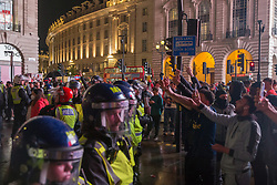 © Licensed to London News Pictures.  12/07/2021. London, UK. Riot police separate Italian football fans who celebrate their victory and England supporters in Piccadilly Circus, central London as England lose to Italy on penalties during the EURO 2020. Photo credit: Marcin Nowak/LNP