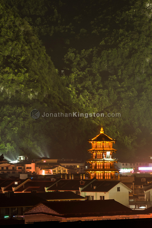 Night view of a red pagoda and the city of Yangshuo, China.