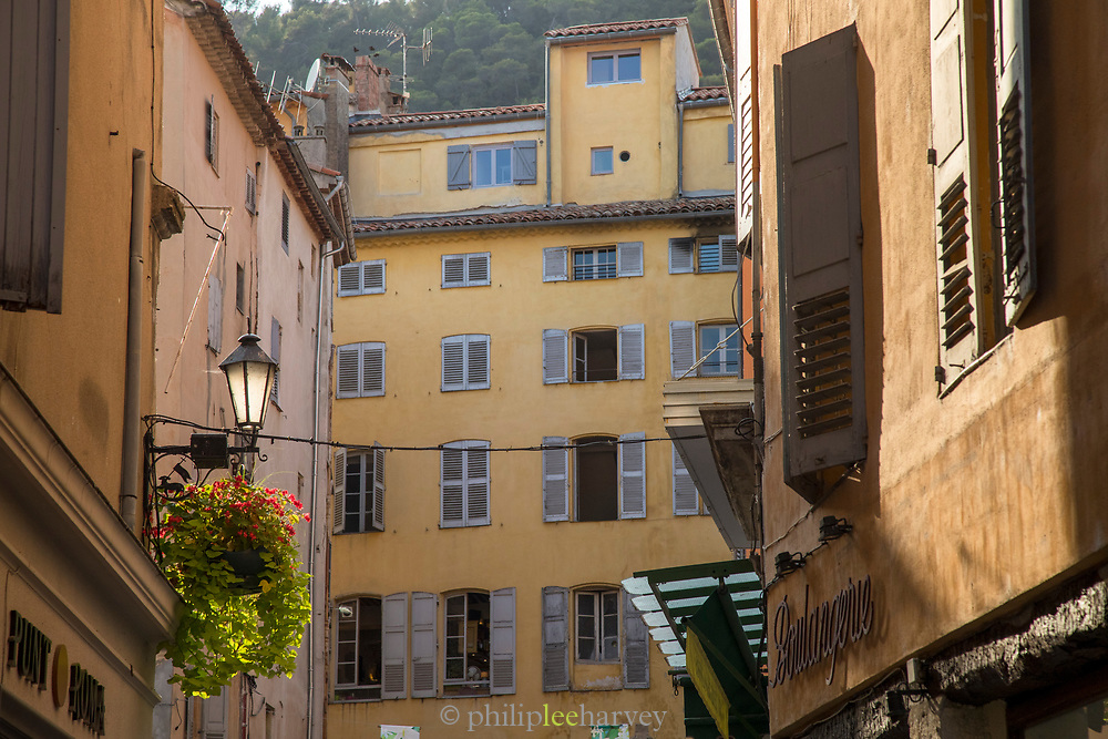 Low angle view of old town tenement houses with shutters, Grasse, France.