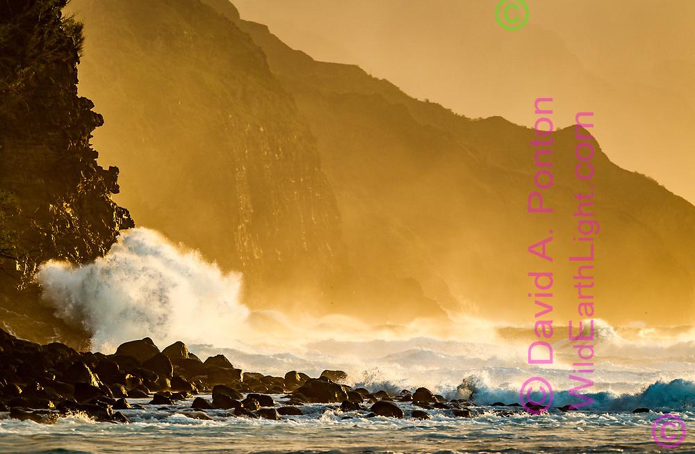 Ocean waves crash against cliffs on the rugged Na Pali Coast, with the light of the setting sun. Kauai, Hawaii, © David A. Ponton