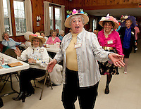 "Norma MacBrien donned with her birds nest Easter bonnet sings ""in your Easter bonnet, with all the frills upon it, you'll be the grandest lady in the easter parade...."" as she marches along with fellow members of  the Laconia Elder Friendship Club during their Easter parade at Leavitt Park Clubhouse Wednesday afternoon.  (Karen Bobotas/for the Laconia Daily Sun)"