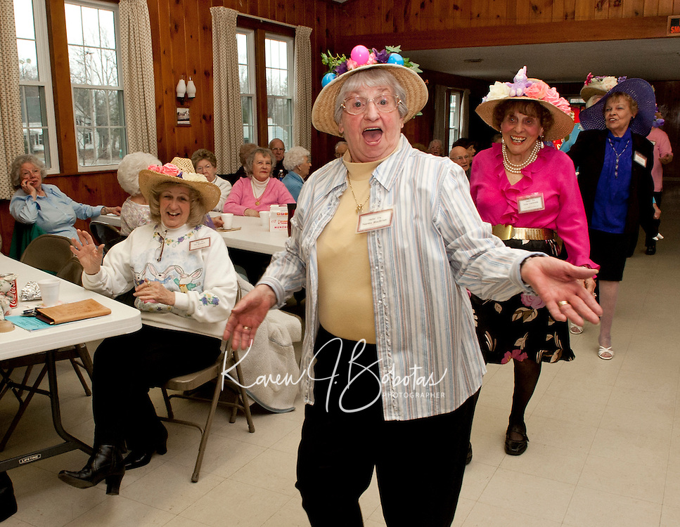"""Norma MacBrien donned with her birds nest Easter bonnet sings """"in your Easter bonnet, with all the frills upon it, you'll be the grandest lady in the easter parade...."""" as she marches along with fellow members of  the Laconia Elder Friendship Club during their Easter parade at Leavitt Park Clubhouse Wednesday afternoon.  (Karen Bobotas/for the Laconia Daily Sun)"""